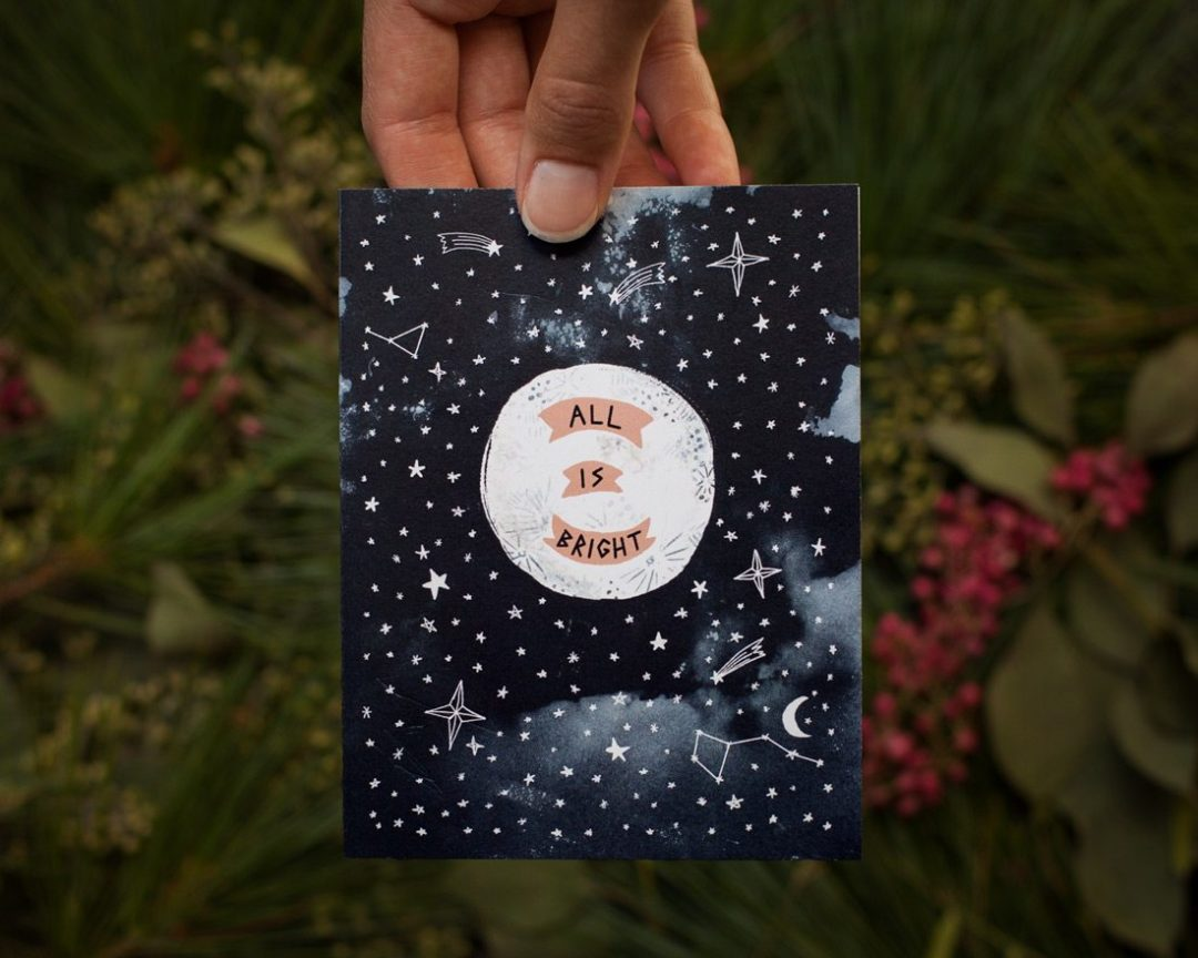 hand holding all is bright with moon holiday card