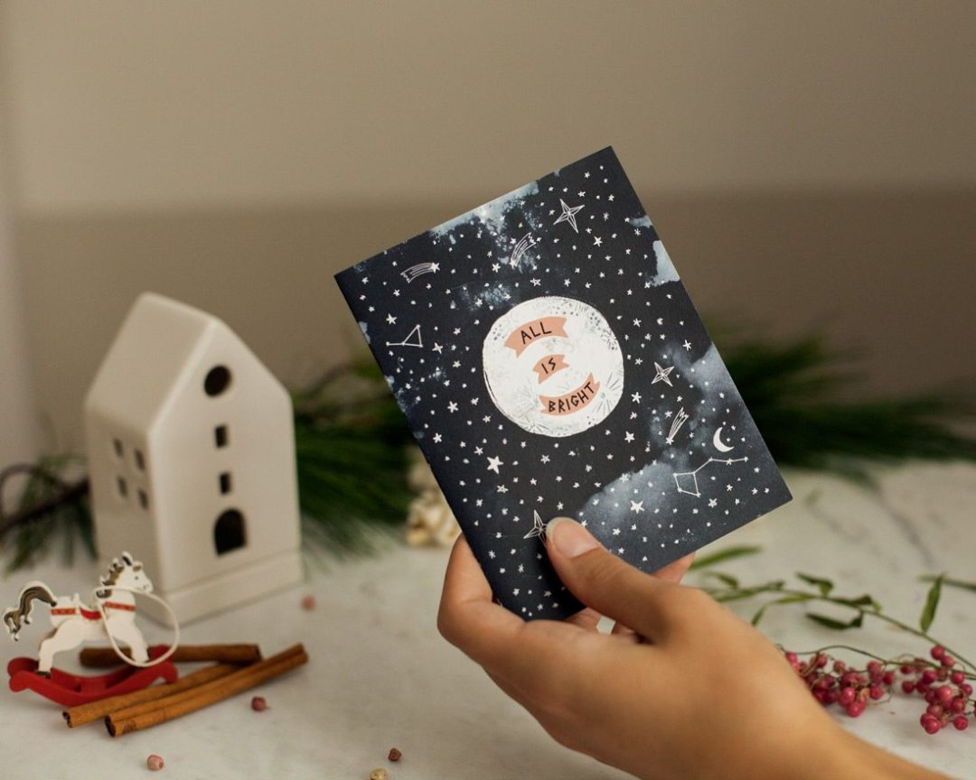 hand holding all is bright moon holiday card