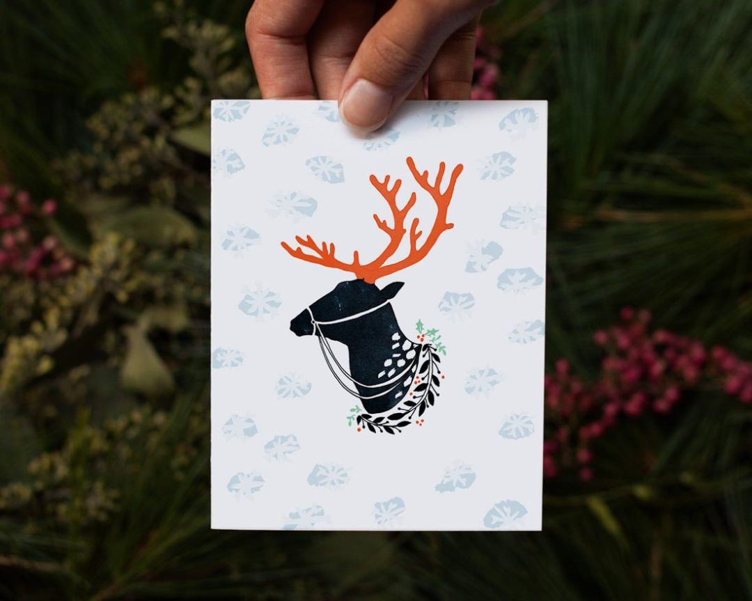 hand holding reindeer christmas card over pine boughs