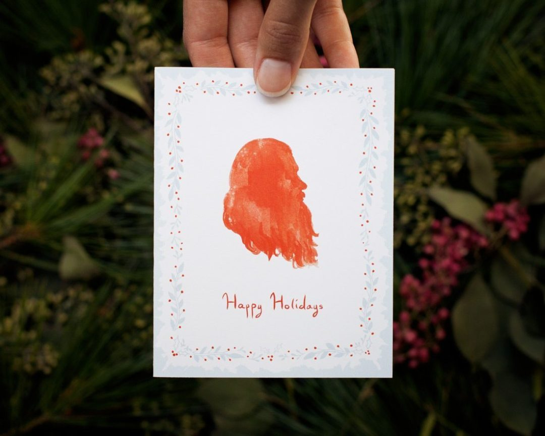 hand holding illustrated Happy Holidays Santa card