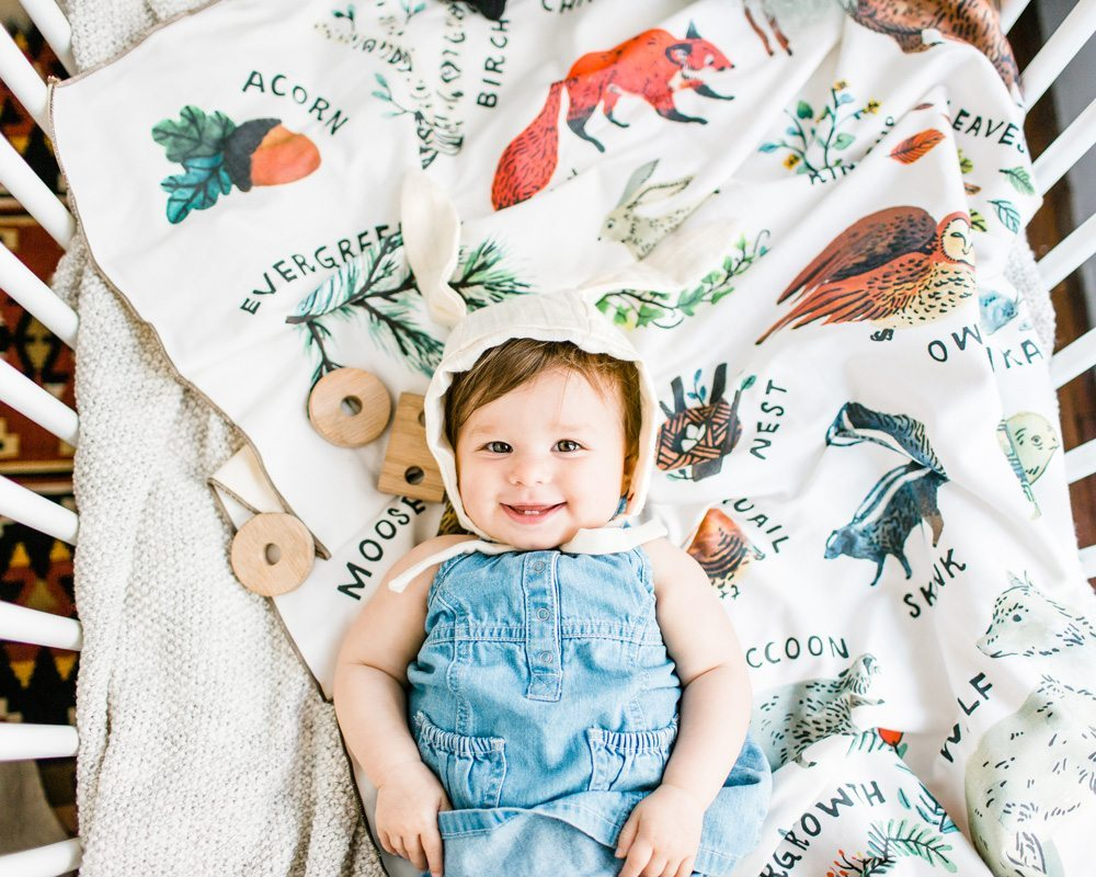baby smiling and laying on organic woodland alphabet baby blanket made in usa