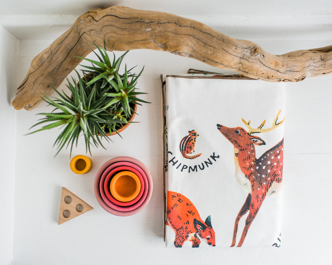 organic woodland alphabet baby blankets made in usa displayed on a white backdrop with plants, driftwood, and colorful wooden baby toys