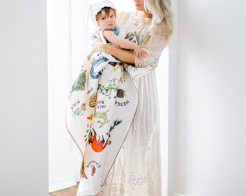 mom and baby snuggling with organic woodland baby blanket made in usa