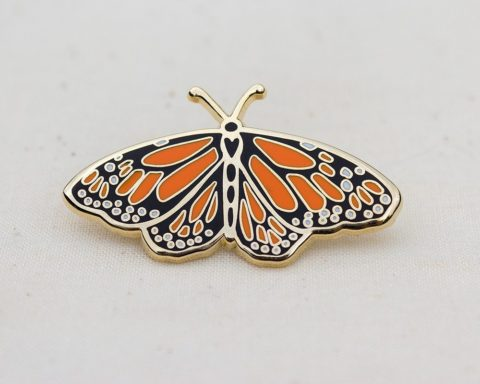 a gold enamel lapel pin of an orange and black monarch butterfly