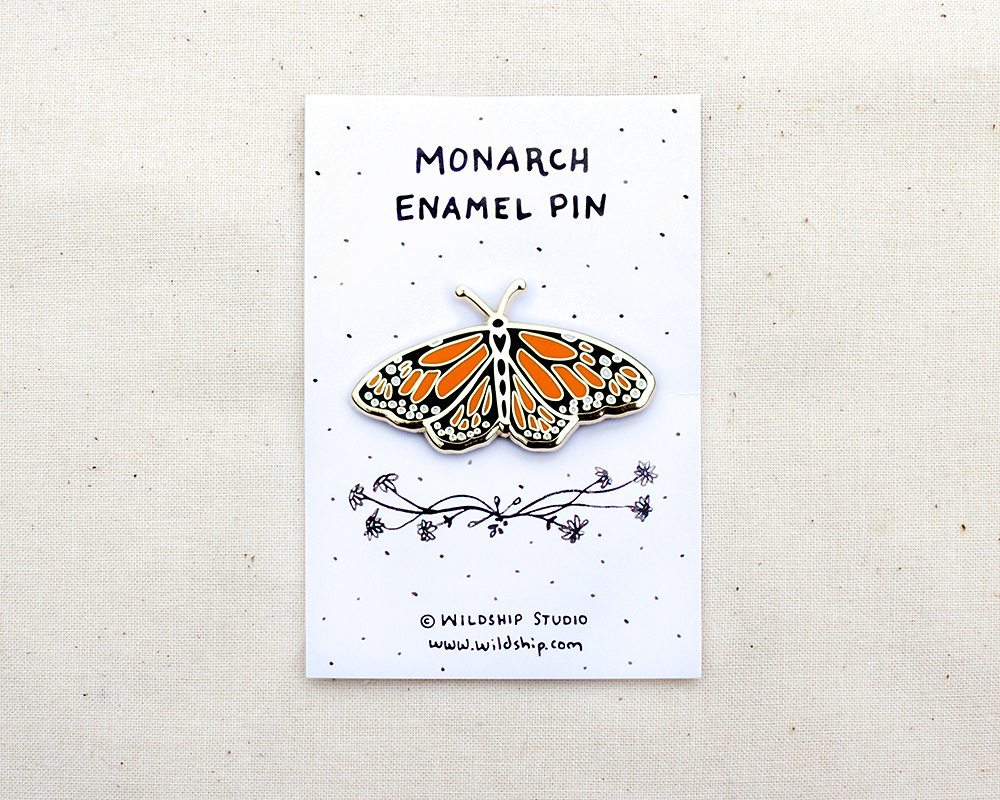 a gold enamel lapel pin of an orange and black monarch butterfly pinned to a backing card
