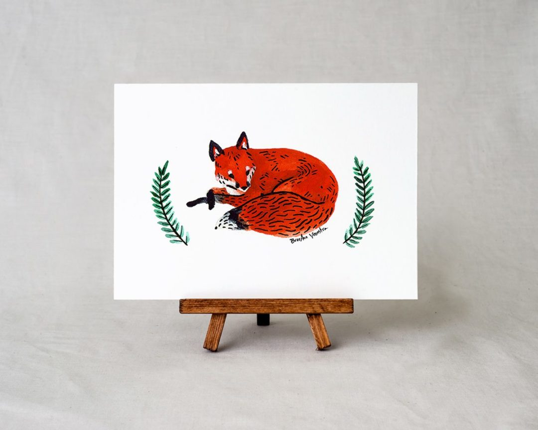 a 5x7 art print on a small easel with a watercolor painting of a red fox laying down with two branches of greenery on either side