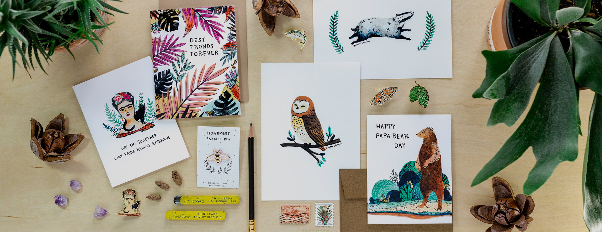 illustrated cards art prints and pins made by wildship studio styled on a light wood backdrop with plants and stamps