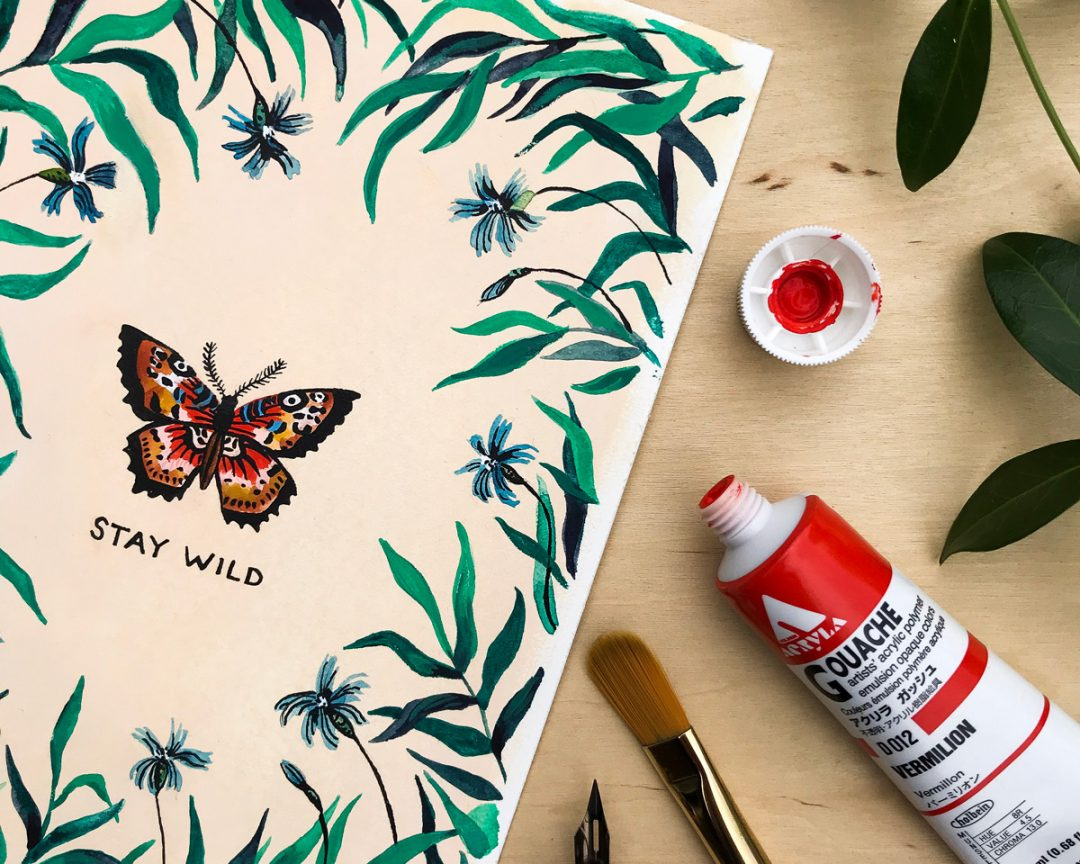 wildship studio watercolor and gouache painting of garden butterfly with green foliage and blue flowers next to a paintbrush and paint tube