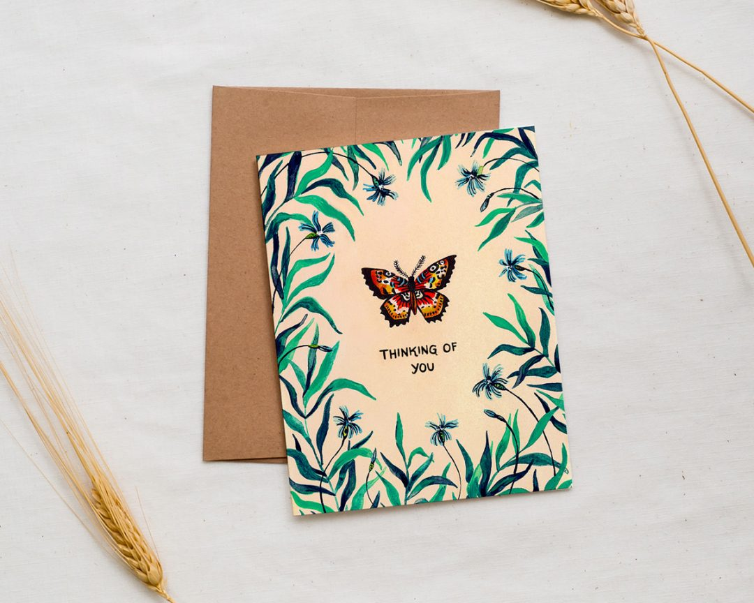 illustrated greeting card with a butterfly surrounded by foliage and text that says thinking of you