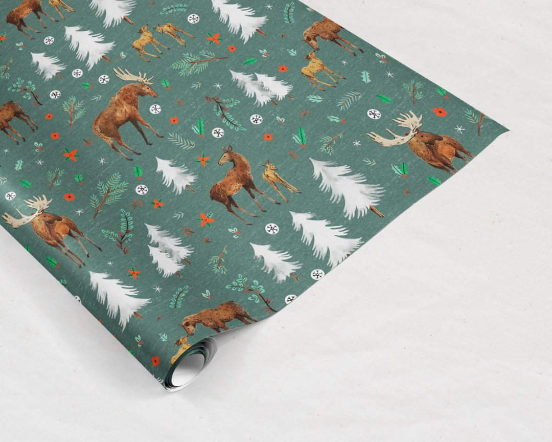 Wildship Studio gift wrapping paper with a charming holiday moose family and alpine trees on a pine green background