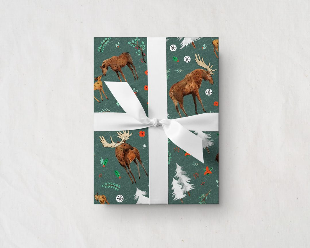 gift with a white ribbon wrapped up in Wildship Studio wrapping paper with a charming holiday moose family and alpine trees on a pine green background