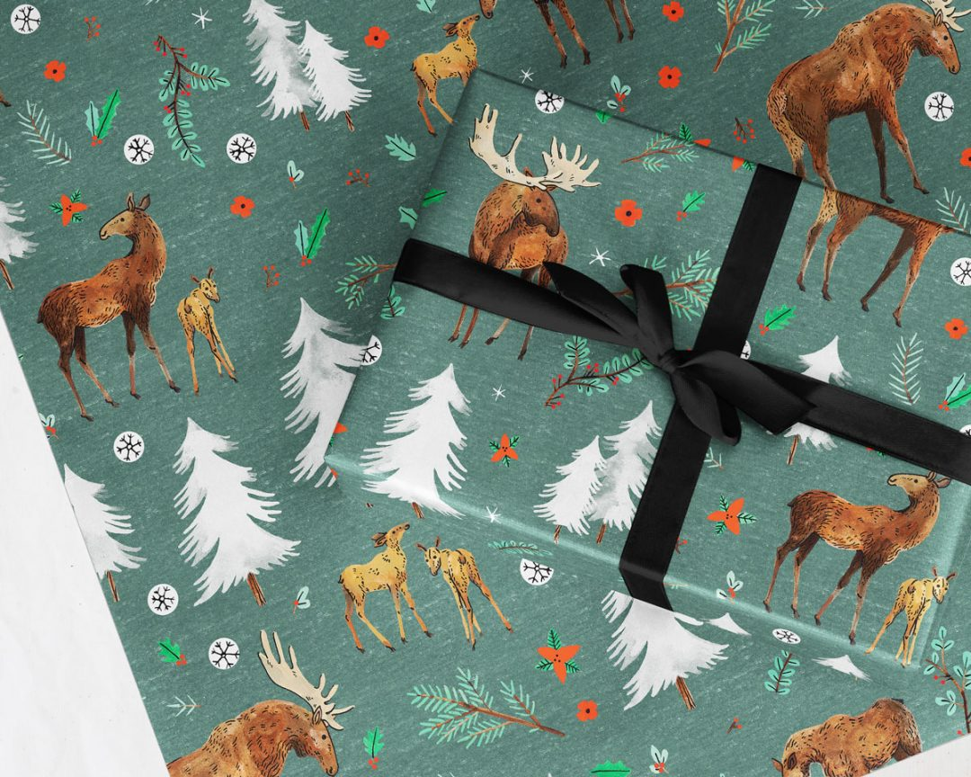 gift with a black ribbon wrapped up in Wildship Studio wrapping paper with a charming holiday moose family and alpine trees on a pine green background