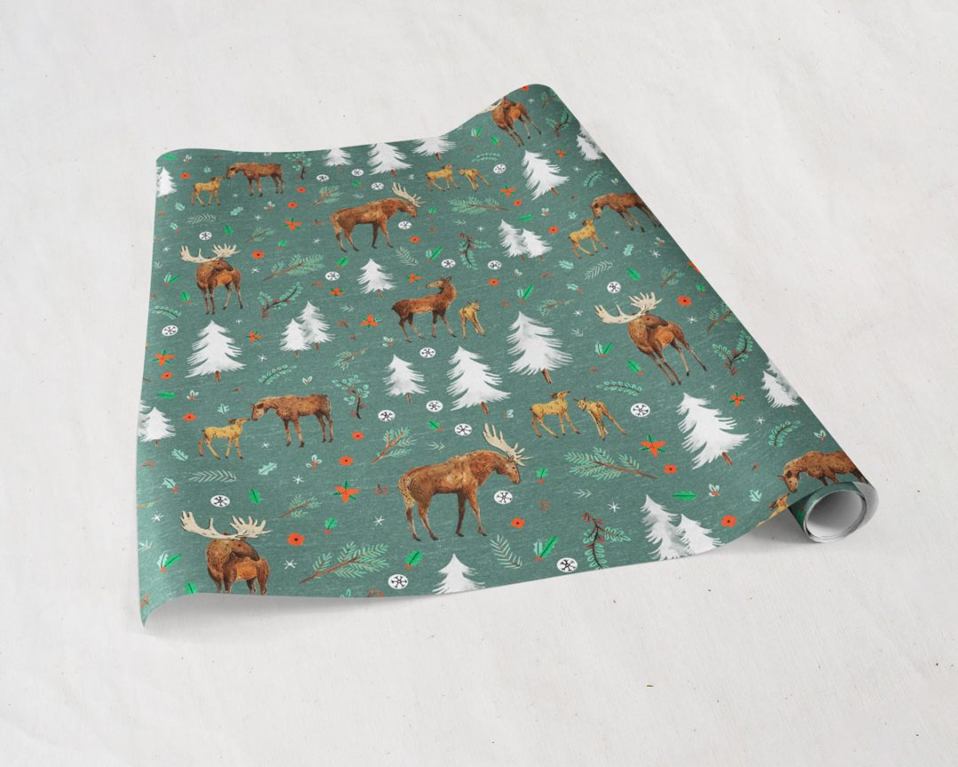 partially unrolled sheets of Wildship Studio gift wrapping paper with a charming holiday moose family and alpine trees on a pine green background