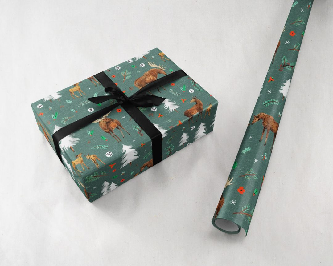 gift with a black ribbon next to a roll of Wildship Studio wrapping paper with a charming holiday moose family and alpine trees on a pine green background