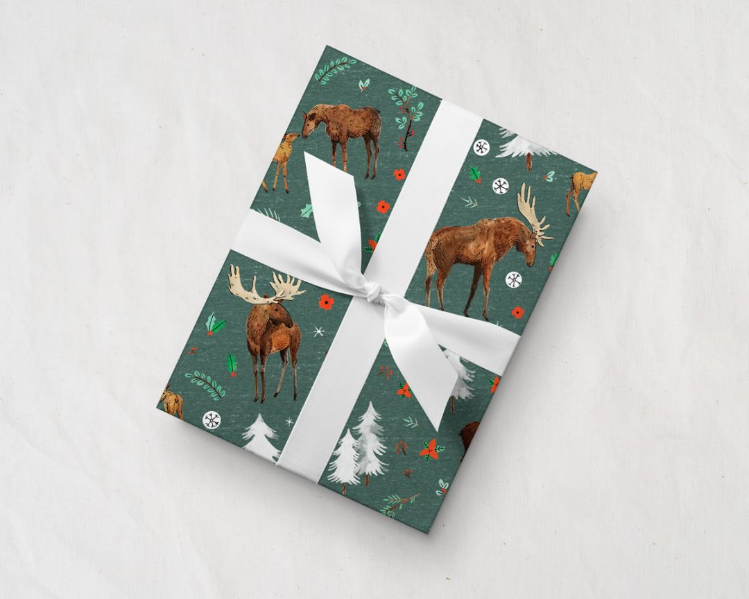tilted gift with a white ribbon wrapped up in Wildship Studio wrapping paper with a charming holiday moose family and alpine trees on a pine green background