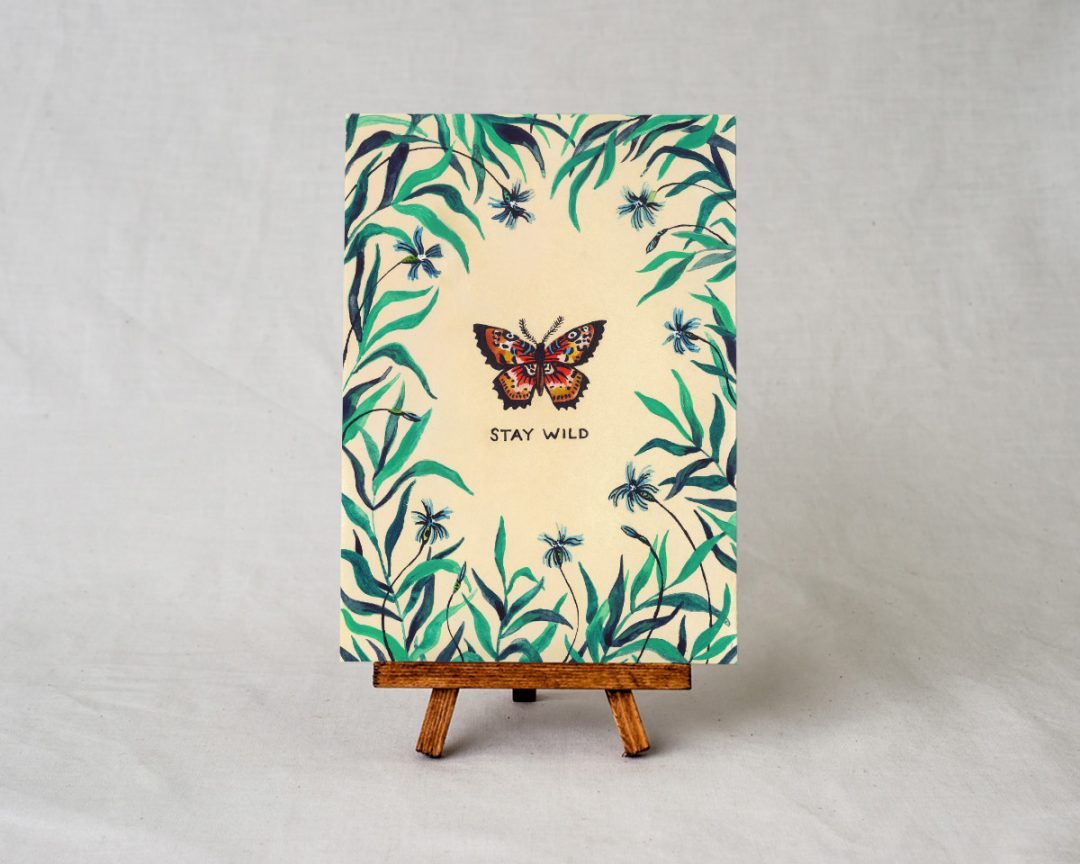 wildship studio art print of garden butterfly with green foliage and blue flowers on a small wooden easel