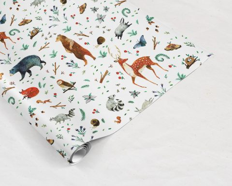 partially unrolled preview of Wildship Studio gift wrapping paper with woodland deer, bears, raccoons, butterflies, foxes, and other animals and flowers