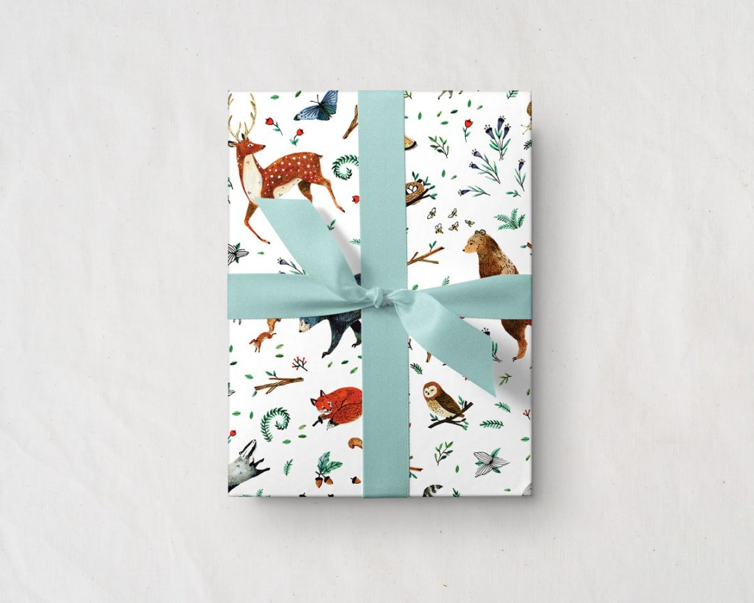 gift with a blue ribbon wrapped up in Wildship Studio gift wrapping paper with woodland deer, bears, raccoons, butterflies, foxes, and other animals and flowers