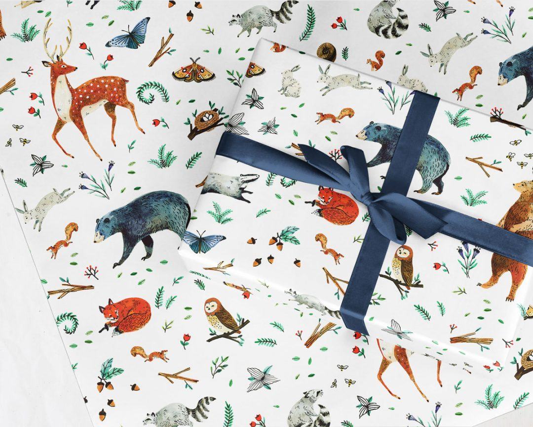 wrapped gift with a navy ribbon bow on a sheet of Wildship Studio gift wrapping paper with woodland deer, bears, raccoons, butterflies, foxes, and other animals and flowers