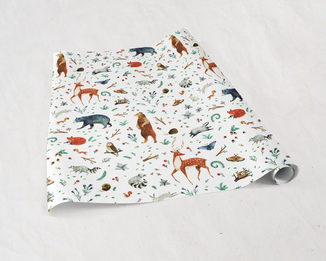 partially unrolled sheets of Wildship Studio gift wrapping paper with woodland deer, bears, raccoons, butterflies, foxes, and other animals and flowers