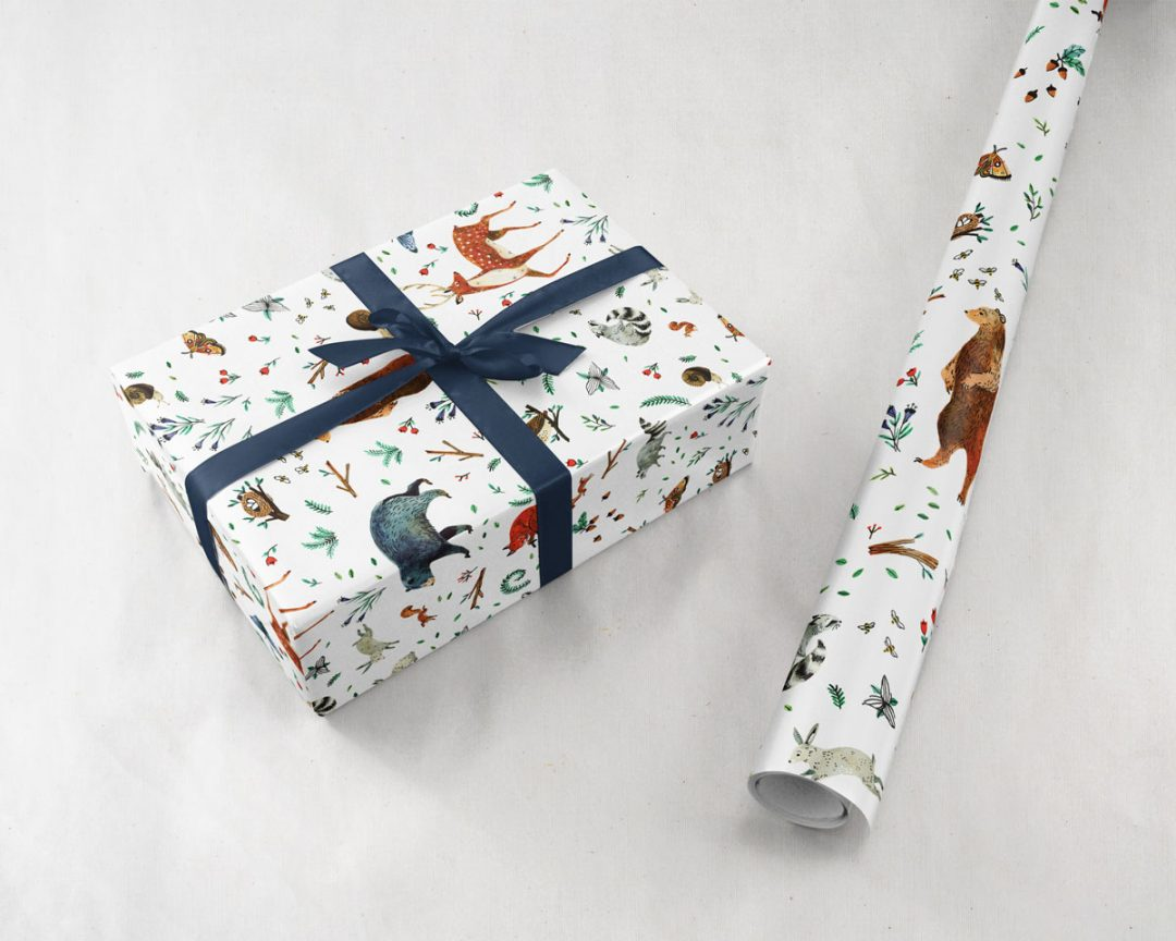 wrapped gift with a navy ribbon next to a roll of Wildship Studio gift wrapping paper with woodland deer, bears, raccoons, butterflies, foxes, and other animals and flowers
