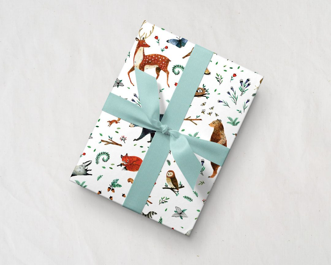 tilted gift with a blue ribbon wrapped up in Wildship Studio gift wrapping paper with woodland deer, bears, raccoons, butterflies, foxes, and other animals and flowers