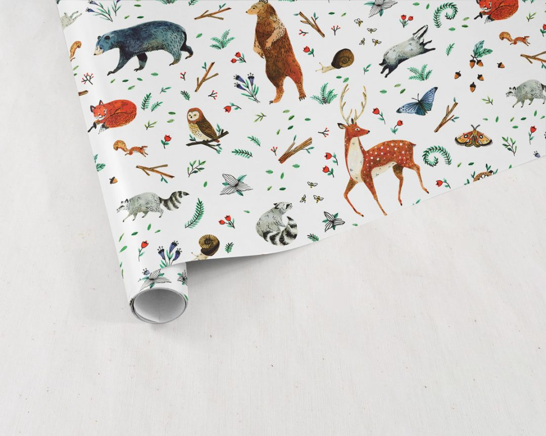 partially unrolled sheet of Wildship Studio gift wrapping paper with woodland deer, bears, raccoons, butterflies, foxes, and other animals and flowers