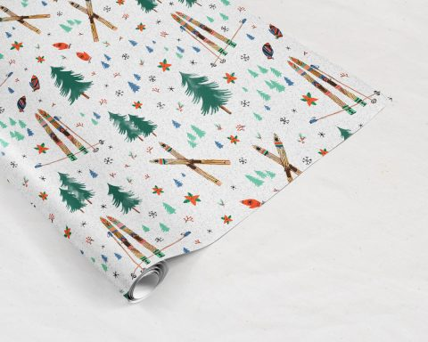Wildship Studio holiday gift wrapping paper with vintage wooden skis, pine trees, snowflakes, poinsettia, and mistletoe