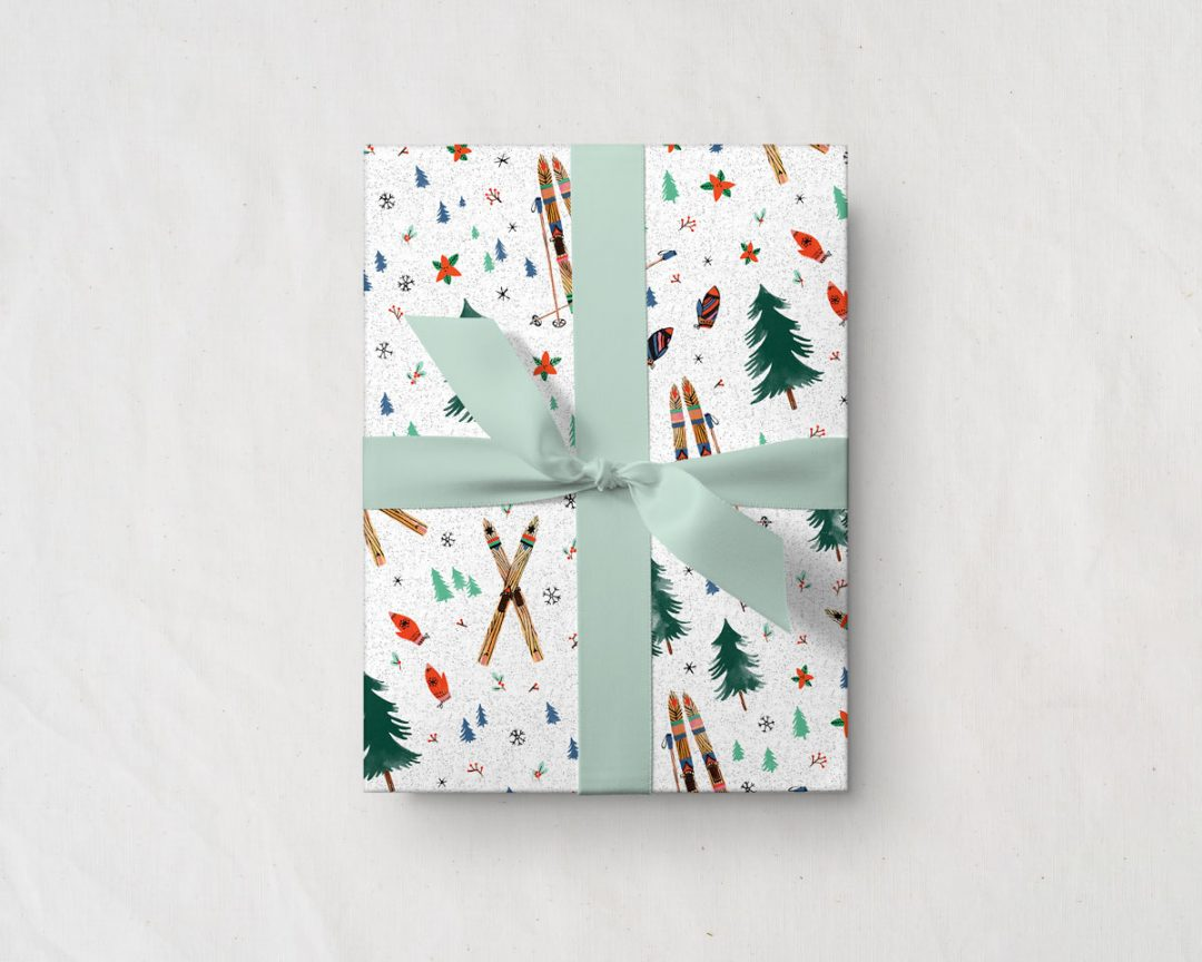 present tied with a green ribbon wrapped up in Wildship Studio holiday gift wrapping paper with vintage wooden skis, pine trees, snowflakes, poinsettia, and mistletoe