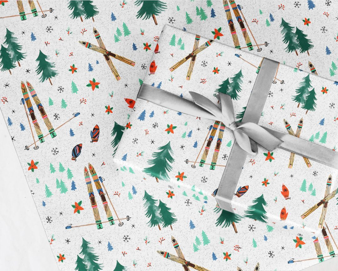 present tied with a silver ribbon wrapped up in Wildship Studio holiday gift wrapping paper with vintage wooden skis, pine trees, snowflakes, poinsettia, and mistletoe