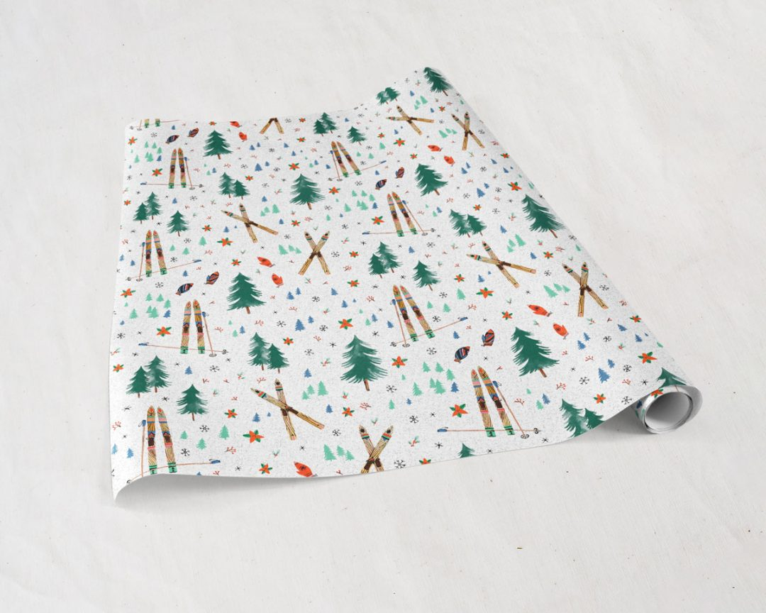 partially unrolled sheets of Wildship Studio holiday gift wrapping paper with vintage wooden skis, pine trees, snowflakes, poinsettia, and mistletoe