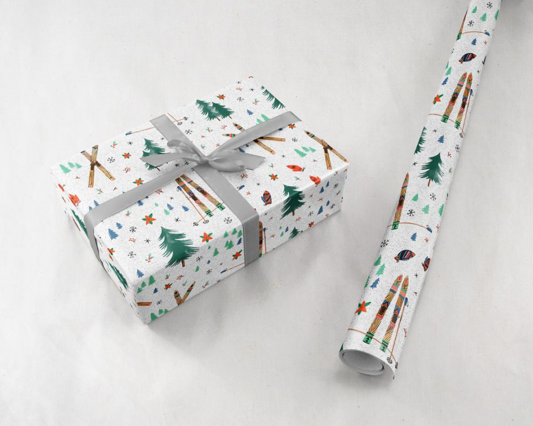 present tied with a silver ribbon next to a roll of Wildship Studio holiday gift wrapping paper with vintage wooden skis, pine trees, snowflakes, poinsettia, and mistletoe