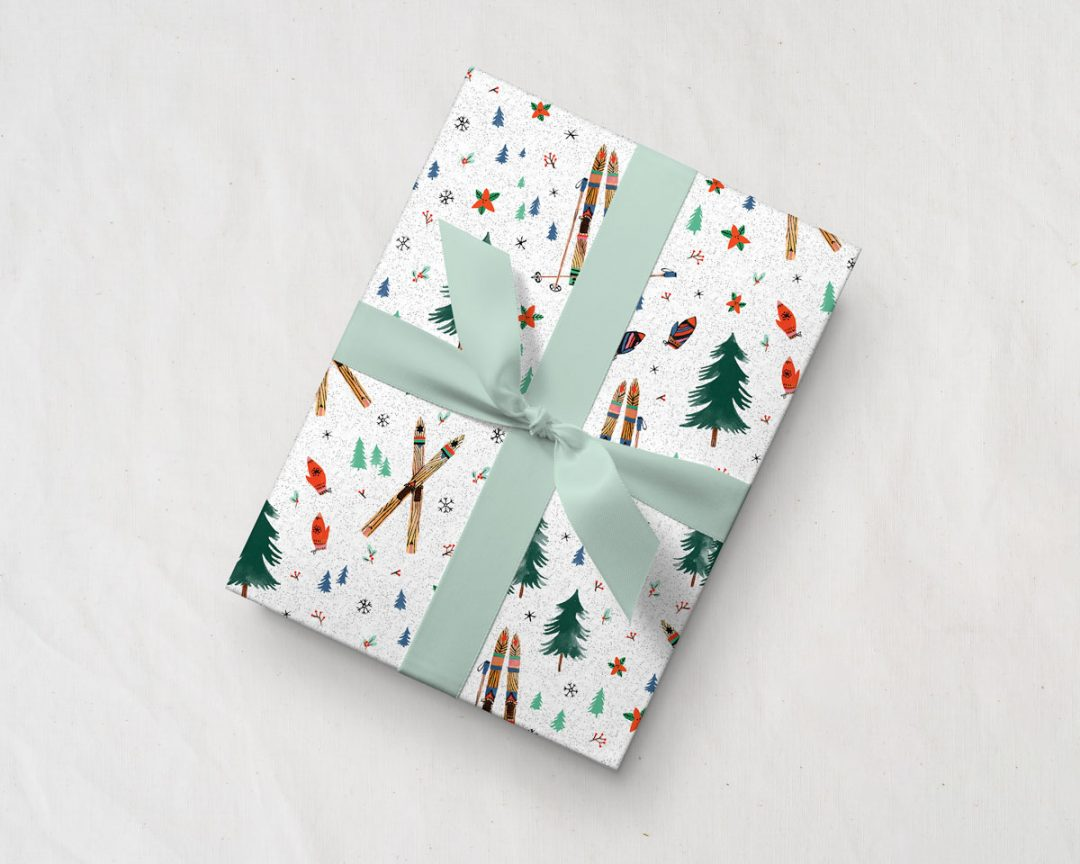 tilted present tied with a green ribbon wrapped up in Wildship Studio holiday gift wrapping paper with vintage wooden skis, pine trees, snowflakes, poinsettia, and mistletoe