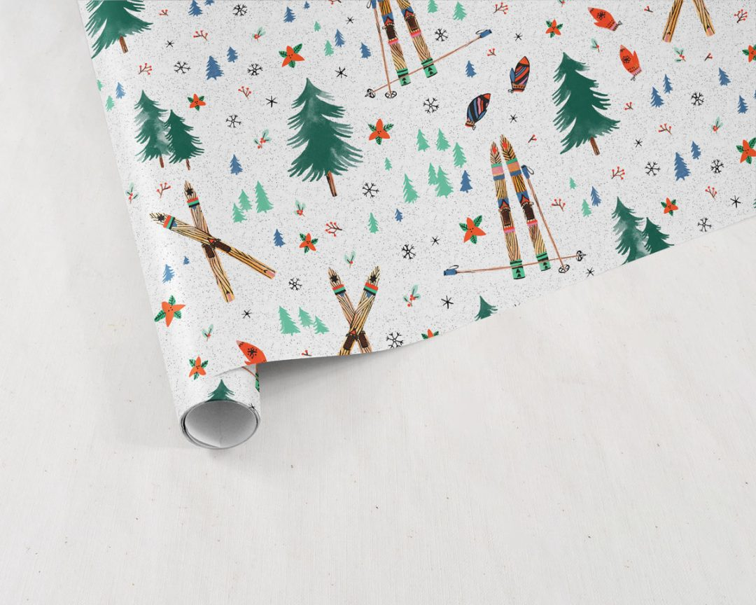 partially unrolled sheet of Wildship Studio holiday gift wrapping paper with vintage wooden skis, pine trees, snowflakes, poinsettia, and mistletoe