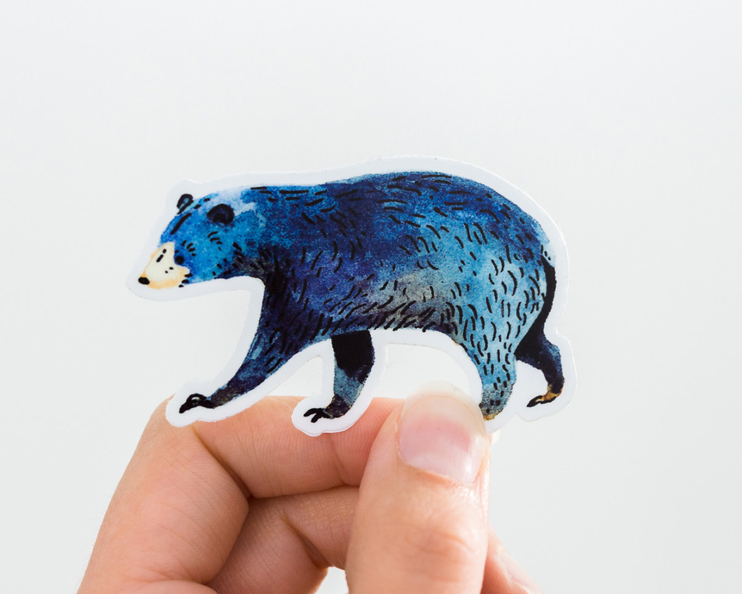 a hand holding a cute black bear vinyl sticker by wildship studio