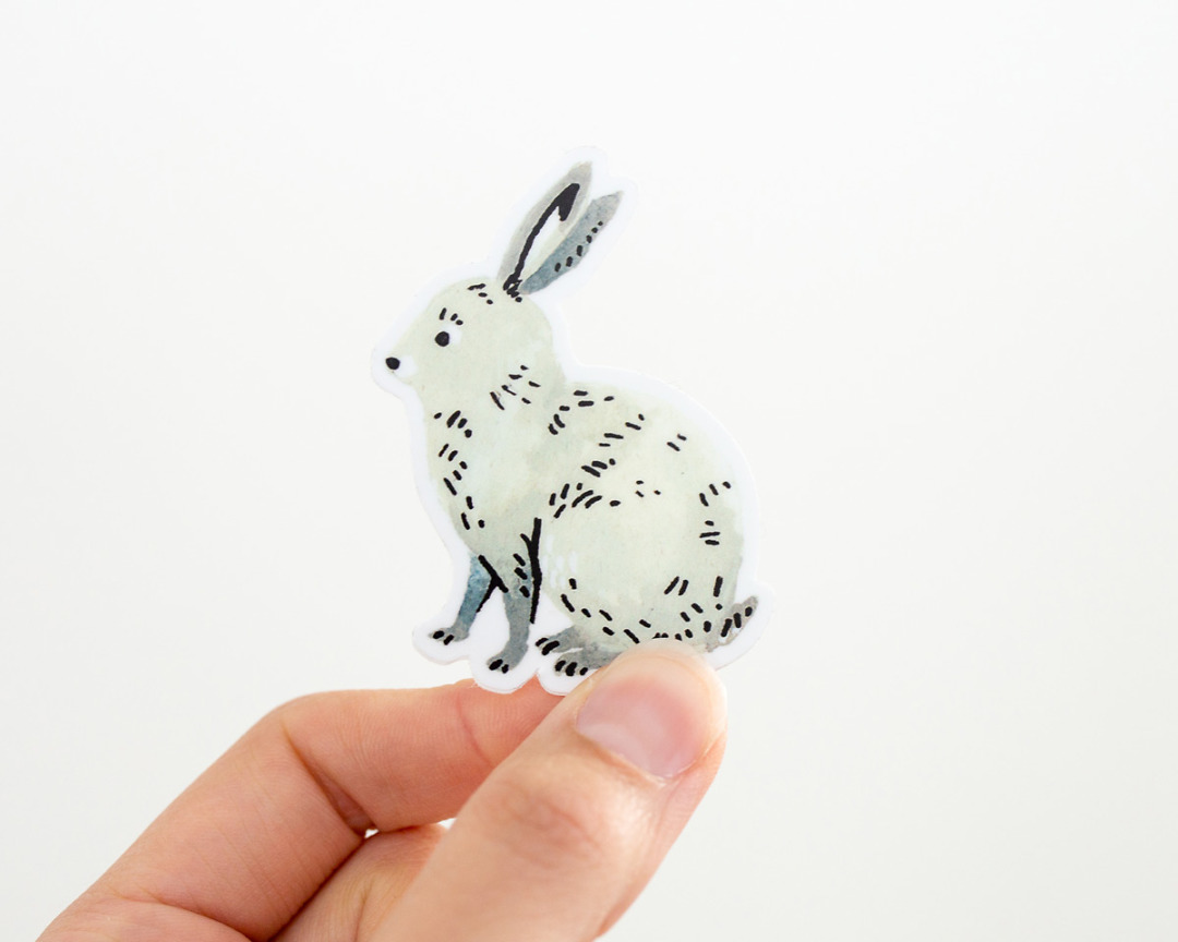 a hand holding a cute bunny rabbit vinyl sticker by wildship studio