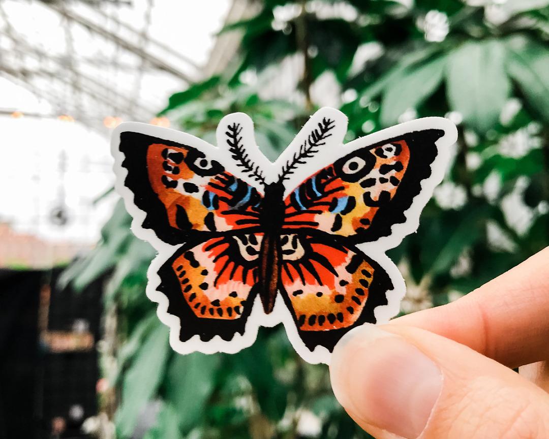 cute butterfly vinyl animal sticker art by wildship studio held against plants