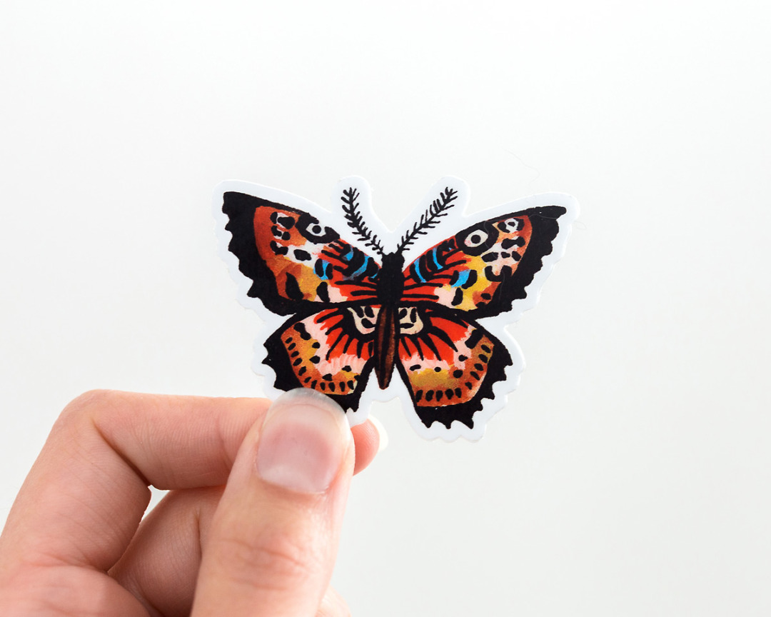 hand holding a cute butterfly vinyl sticker by wildship studio