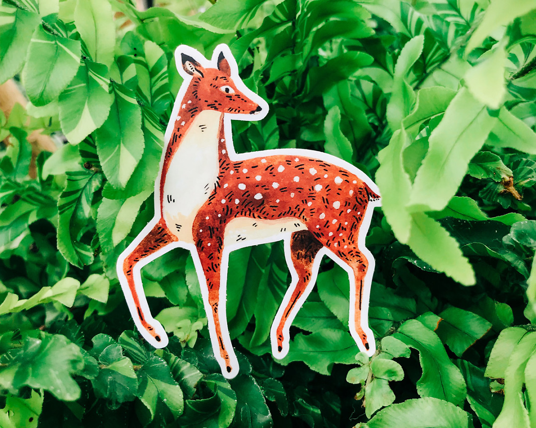 cute deer vinyl animal sticker art by wildship studio against a plant background