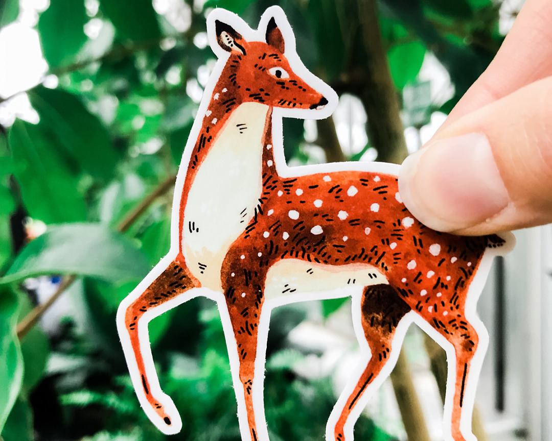 cute deer vinyl animal sticker art by wildship studio held against plants