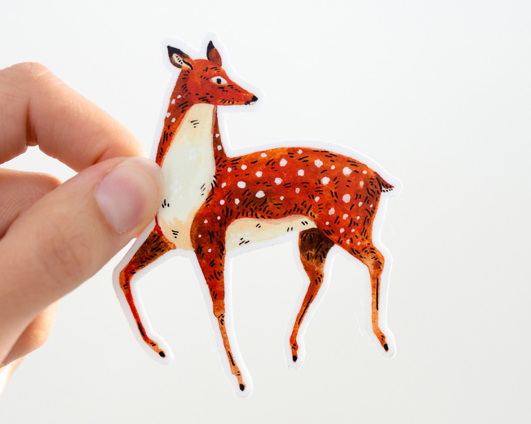 hand holding a cute deer vinyl sticker by wildship studio