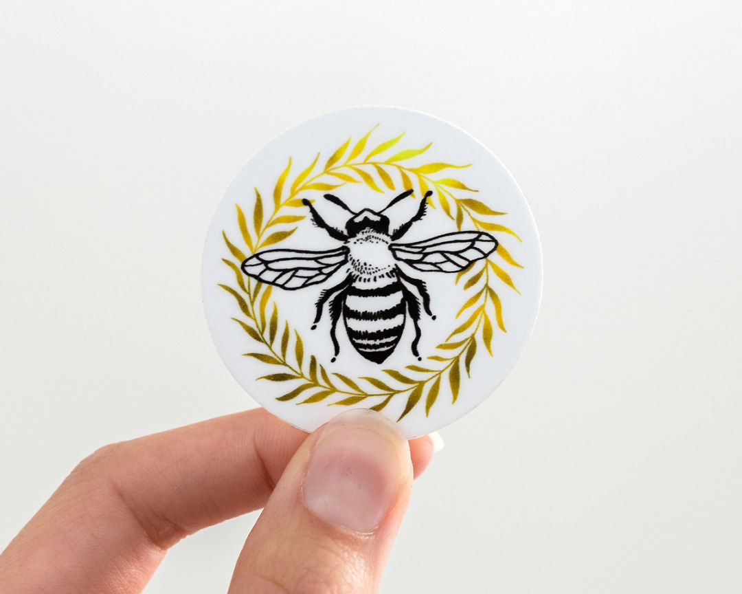 hand holding a cute honey bee and wreath vinyl sticker by wildship studio