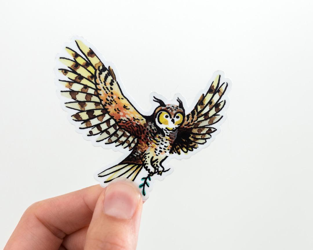 hand holding a cute owl vinyl sticker by wildship studio