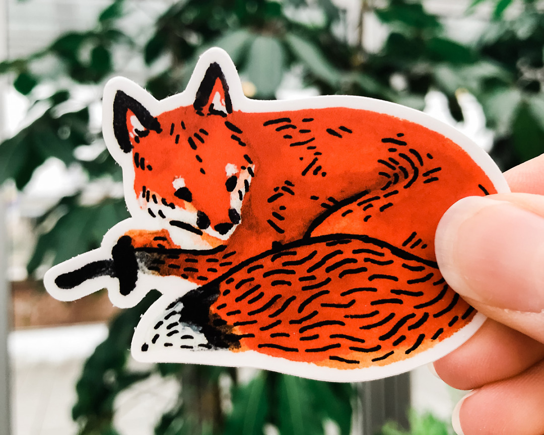 cute red fox vinyl animal sticker art by wildship studio held against plants