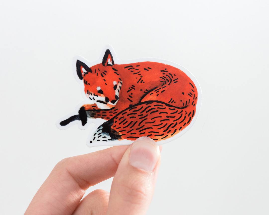 a hand holding a cute red fox vinyl sticker by wildship studio