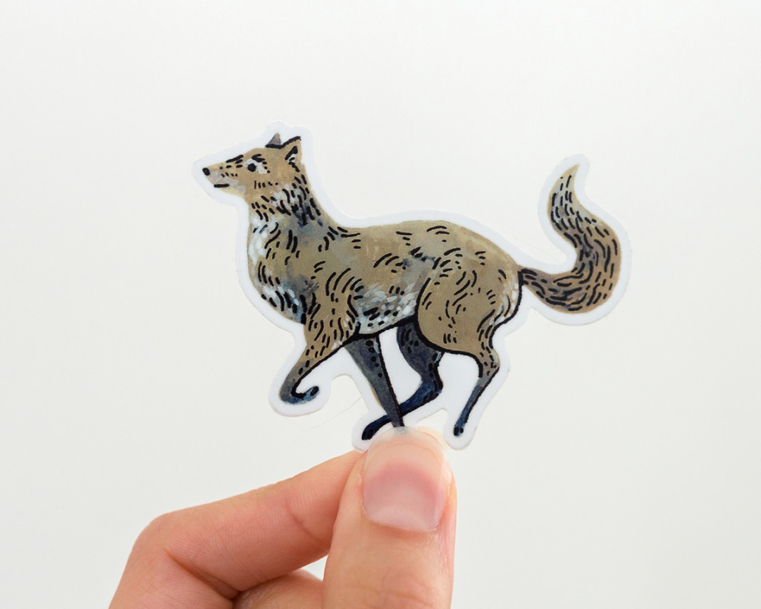 hand holding a cute wolf vinyl sticker by wildship studio