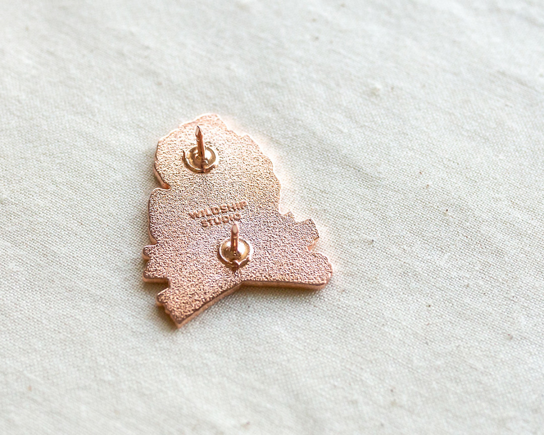 the backside of copper michigan enamel pin