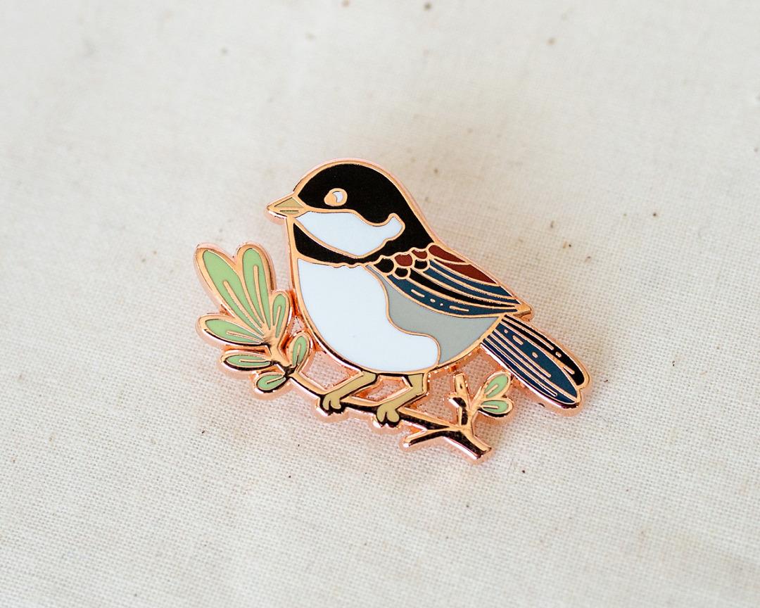 a cute little chickadee enamel pin in copper metal