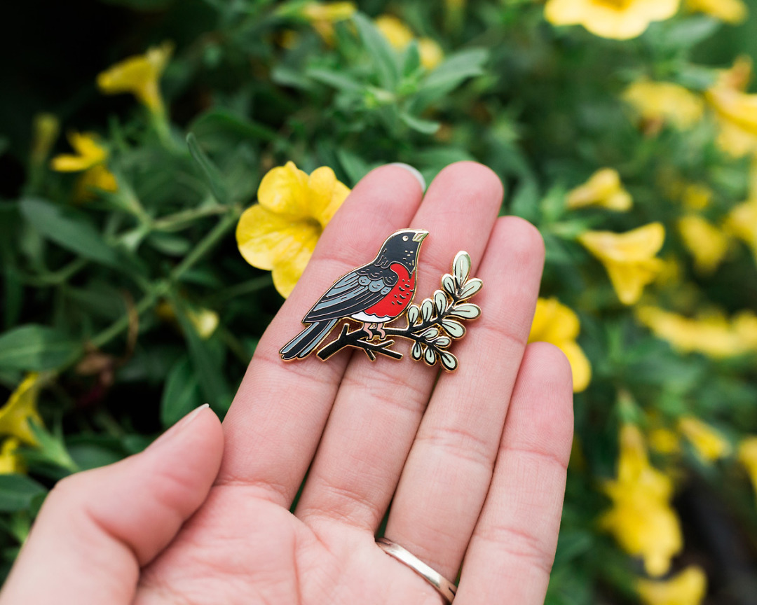 robin enamel pin held in hand with yellow flowers
