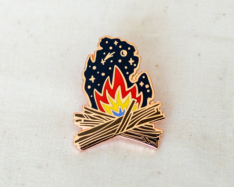 an enamel pin of a campfire and starry night in the shape of michigan